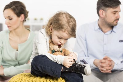 Young family with sad little boy hugging teddy bear and his parents looking depressed