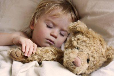 Cute toddler asleep with teddy bear