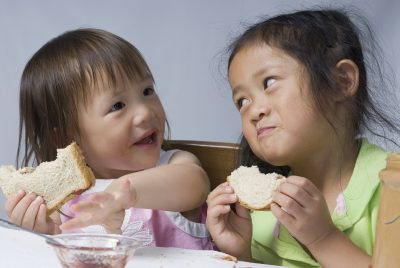 Two sisters making a mess with peanut butter and jelly sandwiches