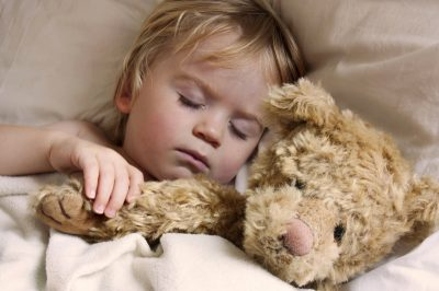 Cute toddler asleep with teddy bear