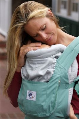 Mother holding baby with baby carrier